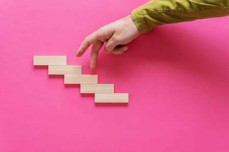 Male hand in causal shirt walking its fingers up the steps made of wooden pegs. Over pink background.