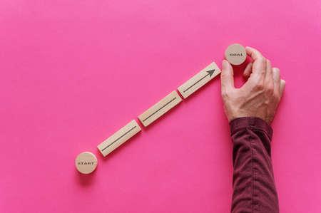 Mano masculina colocando clavijas de madera y círculos para formar un diagrama con la flecha apuntando desde la palabra Inicio a la meta en una imagen conceptual de aspiraciones personales. Sobre fondo rosa. Foto de archivo