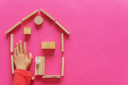 A home made of wooden pegs, blocks and circles with child hand inside it. Over pink background with copy space.