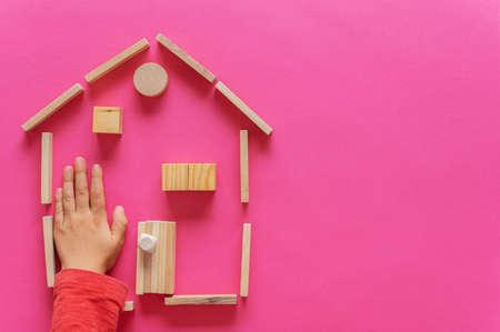 Une maison faite de chevilles, de blocs et de cercles en bois avec une main d'enfant à l'intérieur. Sur fond rose avec espace de copie.