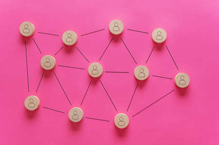 Wooden cut circles with person shape on them placed randomly over pink background connected with black lines in a conceptual image of Customer managed relationship.