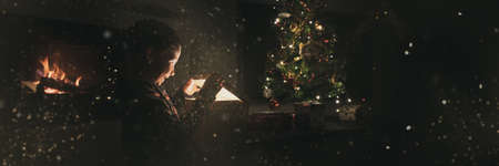 Wide view image of an excited boy opening a holiday gift box under Christmas tree next to a fireplace. With glitters and fairy dust all over the image.