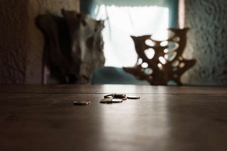 Euro coins on wooden desk in an older house in a conceptual image of poverty. 写真素材