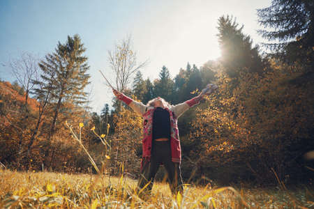 Homeless man in torn sweater celebrating life holding his violin standing in golden autumn nature.