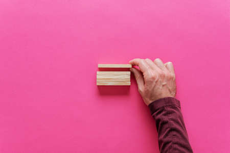 Male hand stacking blank wooden pegs in a conceptual image. Over pink background with copy space. Stock fotó