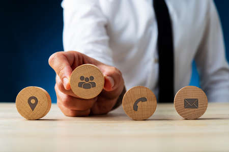 Business customer service representative placing four wooden cut circles with contact and information icons on them in a row.