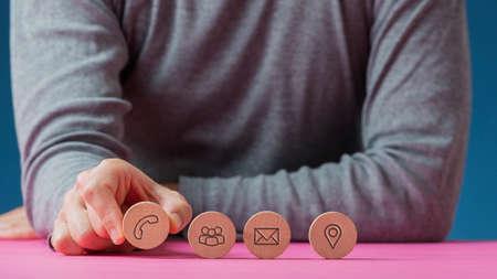 Vista frontal de un hombre colocando cuatro círculos cortados de madera con iconos de contacto y comunicación en una fila en el escritorio rosa.