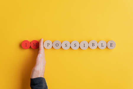 Male hand separating letters IM from the word Impossible spelled on wooden cut circles in a conceptual image. Over yellow background.