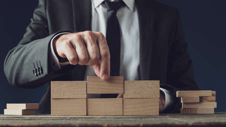 Front view of a businessman building a structure of wooden pegs in a conceptual image of business vision and start up. Stok Fotoğraf
