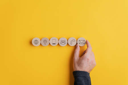 Male hand placing six wooden cut circles with contact and communication icons on them in a row over yellow background. Standard-Bild