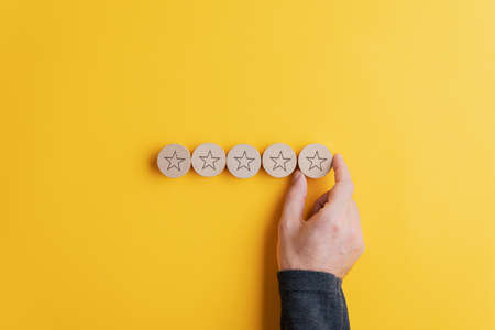 Male hand placing five wooden cut circles with stars on them in a row over bright yellow background. Conceptual image of quality and service. Standard-Bild