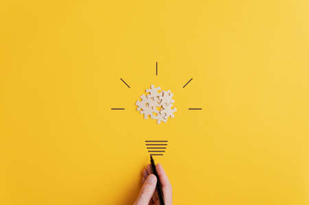 Light bulb of blank puzzle pieces as the bulb and hand drawn neck and rays over yellow background in a conceptual image of vision and idea.