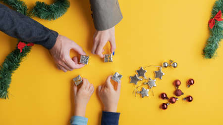 Top view of a family of four placing four mini presents on yellow background with holiday ornaments scattered around in a conceptual image.
