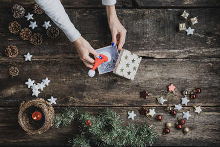Top view of female hand placing red Santa hat and silver stars in a gift box on a rustic wooden desk with holiday decoration, candle and pine tree branches on it. Stock Photo