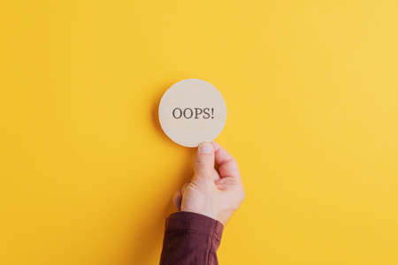 Male hand placing wooden cut circle with an Oops sign on it on bright yellow background. Zdjęcie Seryjne