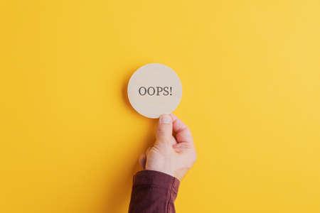 Mano maschile posizionando un cerchio tagliato in legno con un segno Oops su di esso su sfondo giallo brillante. Archivio Fotografico