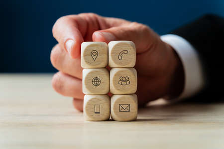 Businessman stacking wooden dices with icons of contact and information on them in a conceptual image of business support and service. Stok Fotoğraf