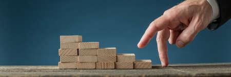 Homme d'affaires sur le point de monter ses doigts dans les escaliers faits de chevilles en bois dans une image conceptuelle de la détermination et de l'ambition des entreprises. Banque d'images