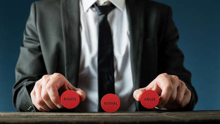 Businessman holding red wooden cut circles with animal right and animal abuse sign in a conceptual image.