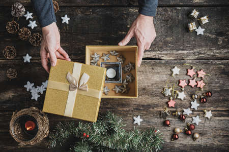Top view of male hands packing a holiday gift box with candle and silver stars in it on a rustic wooden desk with Christmas decorations and ornaments scattered around. Stock Photo