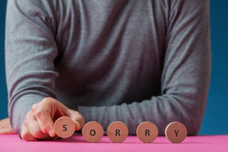 Front view of a man making a Sorry sign spelled on wooden cut circles.