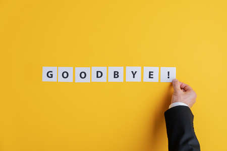 Hand of a businessman assembling a Goodbye sign with white post it papers over yellow background. With copy space.