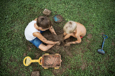 Top view of two brothers sitting on green grass playing with mud covering their legs in it.