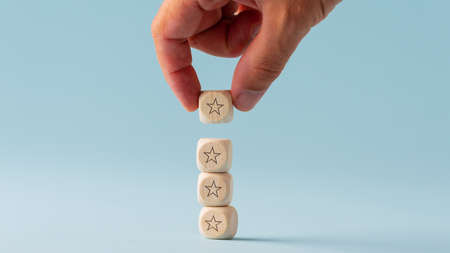 Male hand stacking five wooden dices with star shape on them in a conceptual image. Over bright blue background.