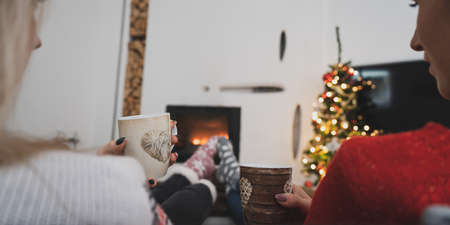 View from behind of two girlfriends with warm socks sitting by the fireplace and Christmas tree drinking coffee or tea.