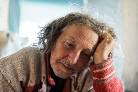 Porträt eines älteren Mannes in zerrissenem Pullover mit besorgtem und müdem Ausdruck auf seinem Gesicht, das sich in seinen Arm lehnt.