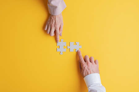 Hands of a businessman and businesswoman each placing one blank puzzle piece over yellow background.