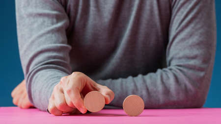 Male hand placing one blank wooden cut circles next to the other in a conceptual image of personal choice or preference. 版權商用圖片