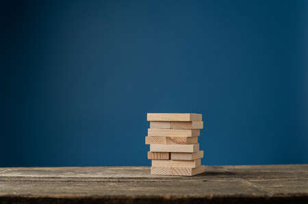 Blank wooden pegs stacked on rustic wooden desk in a conceptual image. Over dark blue background.