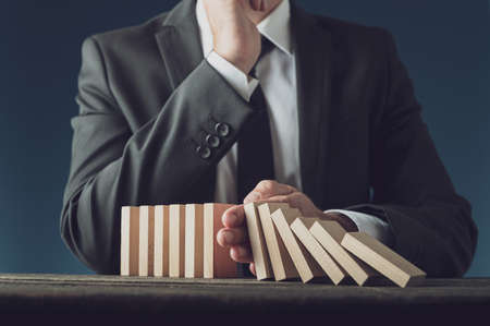 Front view of successful business crisis manager stopping collapsing dominos in a conceptual image.