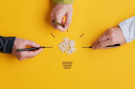 Three male hands drawing a light bulb with puzzle pieces in the middle in a conceptual image of vision and teamwork. Over yellow background. Stock Photo