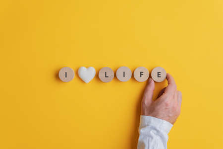 Male hand making an I love life sign spelled on wooden cut circles with marble heart in the middle. Over yellow background with copy space.