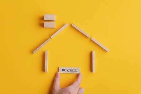 Mano masculina colocando un cartel de compra / venta en una casa hecha de bloques de madera y clavijas en una imagen conceptual del mercado inmobiliario. Sobre fondo amarillo.