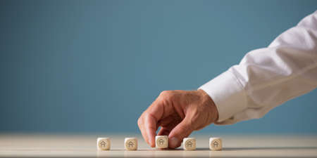 Hand of a realtor placing five wooden dices with house shape on them in a row in a conceptual image of real estate market. With copy space. Banque d'images