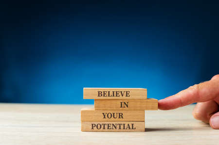 Believe in your potential sign written on wooden pegs.