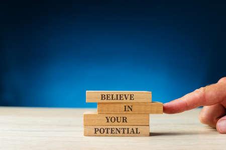 Croyez en votre signe potentiel écrit sur des chevilles en bois.
