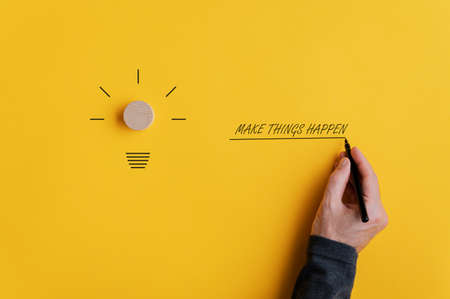 Male hand writing a Make things happen sign next to a light bulb shape over yellow background. 版權商用圖片