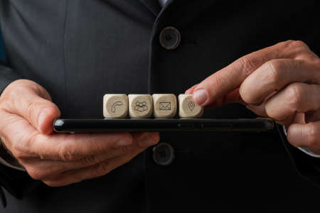 Customer service representative placing wooden dices with contact and information icons on digital tablet.