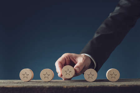 Businessman placing five wooden cut circles with star shape on them in a row on a desk in conceptual image of quality and trust. Reklamní fotografie