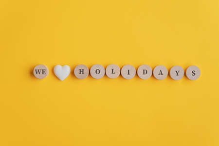 We love holidays sign spelled on wooden cut circles with heart shape marble in the middle. Over yellow background.