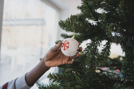Closeup image of colored girl holding white holiday bauble with red snowflake on it hanging on Christmas tree. Stock Photo
