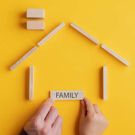 Child and son placing a wooden peg with Family sign on it in a house made of wooden blocks in a conceptual image. Over yellow background.