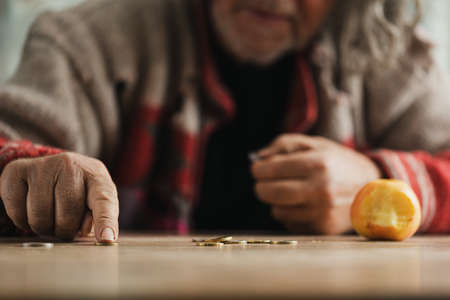 Low angle view of senior homeless man counting coins with a bitten apple on a desk.