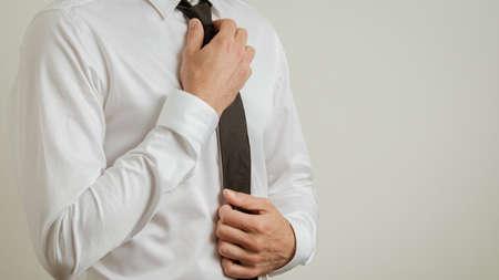 Torso de hombre de negocios en elegante camisa blanca atando su corbata negra. Con espacio de copia en el lado derecho de una imagen.