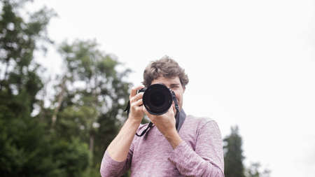Young man taking a photo with dslr camera directly at you. Foto de archivo - 136585877