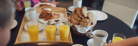 Generous breakfast table of a family on vacation full of orange juice, bread, croissants, coffee and spreads. Wide view image.